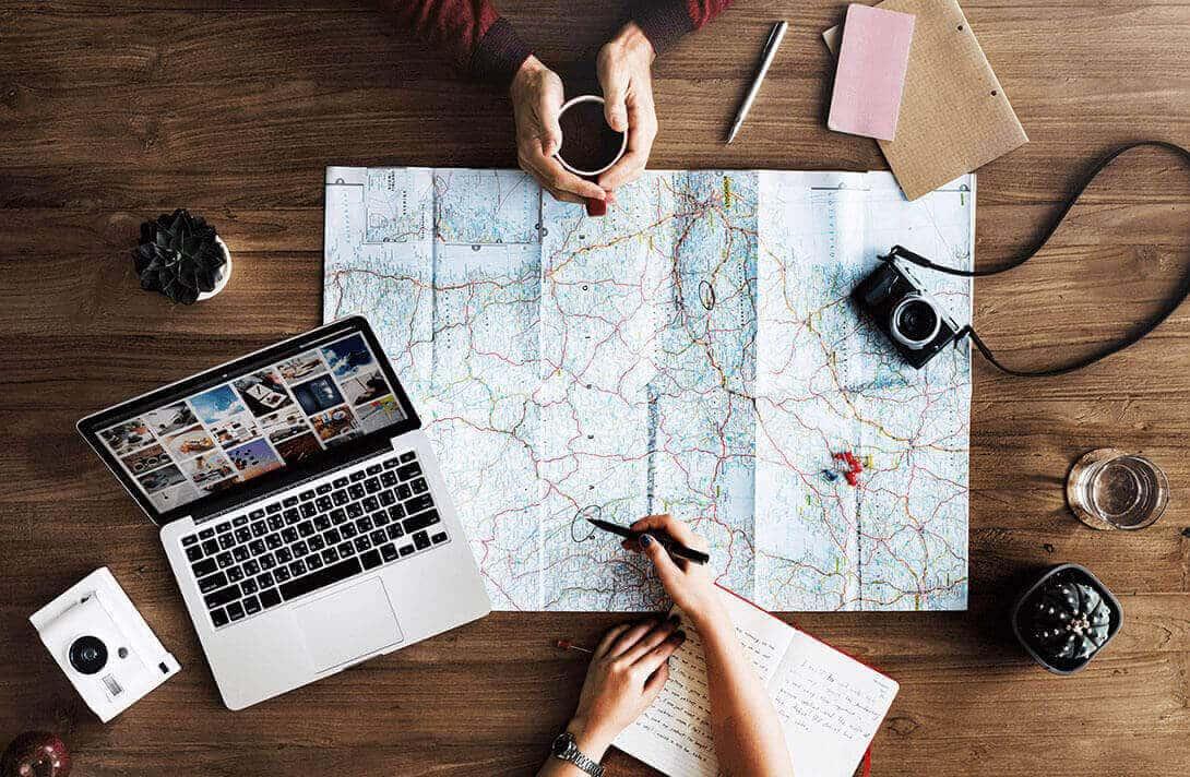 Reiseplanung mit Landkarte und Macbook Pro