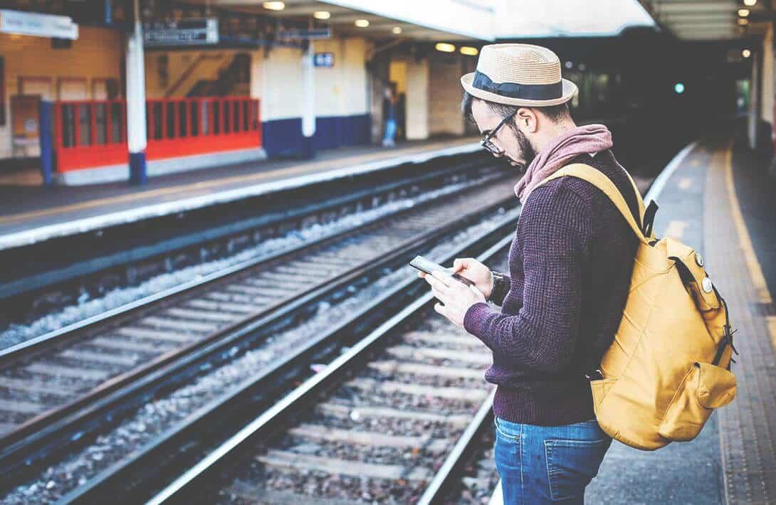 Mann mit Smartphone an Bahngleis